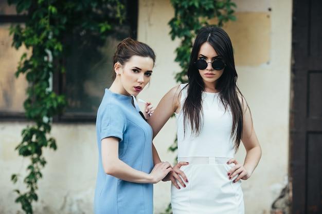 Due belle ragazze in abiti in posa davanti a casa