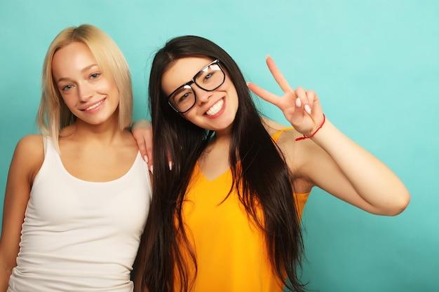 Due belle ragazze che danno il segno della mano di vittoria