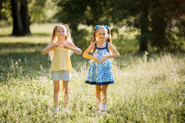 Due belle giovani ragazze gioiose in estate in un parco con gesti delle mani a forma di cuori