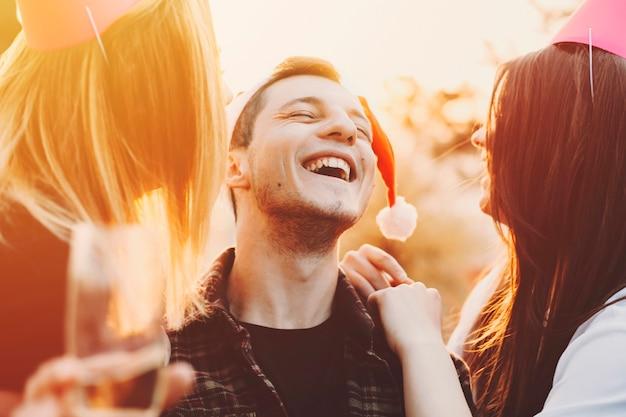Due belle giovani donne in cappelli da festa ridendo e guardando allegro ragazzo con un bicchiere di alcol mentre celebravano il natale nella natura.