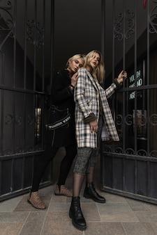 Due belle giovani sorelle con capelli biondi con labbra sexy in abiti vintage con stivali alla moda stanno vicino al cancello di ferro in città