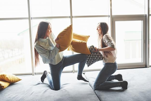 Due belle sorelle gemelle giovani che trascorrono del tempo insieme e stanno combattendo con i cuscini. fratelli germani divertendosi a casa concetto