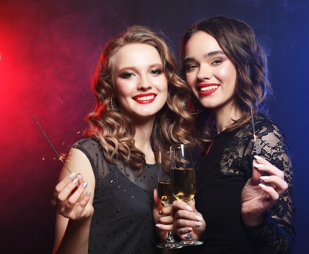 Due belle giovani donne in abito nero con bicchieri di vino e scintilla di fuoco.