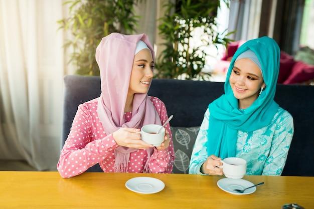 Due belle giovani donne bevono il tè in un ristorante in abiti musulmani