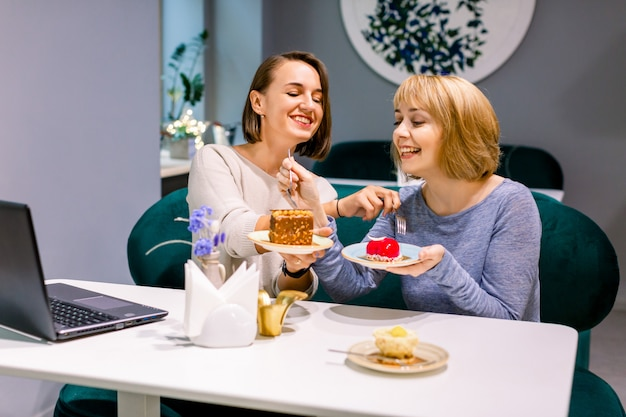 Due belle giovani donne che godono insieme del caffè e della torta in un caffè che si siede ad una tavola che ride e che chiacchiera con i sorrisi felici
