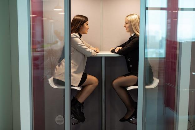 Due belle giovani donne negoziano in una riunione