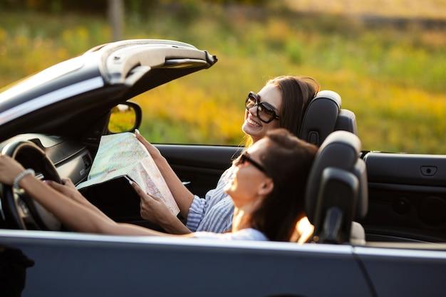 Due belle giovani donne in occhiali da sole sono sedute in una cabriolet nera e sorridono in una giornata di sole. uno di loro tiene la mappa nelle sue mani. .