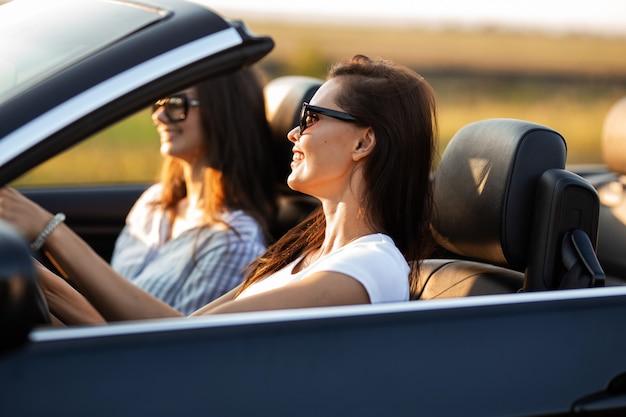 Due belle giovani donne in occhiali da sole sono sedute in una cabriolet nera e sorridono in una giornata di sole. .