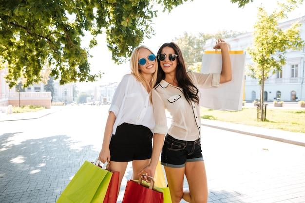 Due belle giovani donne che camminano insieme lungo la strada e che tengono le borse della spesa