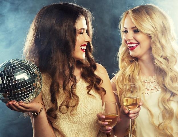 Due belle giovani donne con bicchieri di vino e palla da discoteca.
