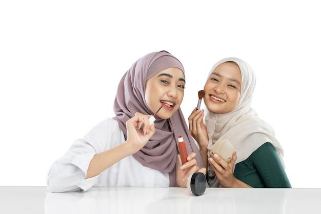 Due ragazze velate di bellezza che tengono il pennello e applicano il rossetto durante la realizzazione di video