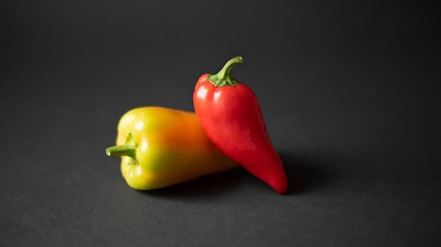 Due peperoni di colore diverso su sfondo nero scuro