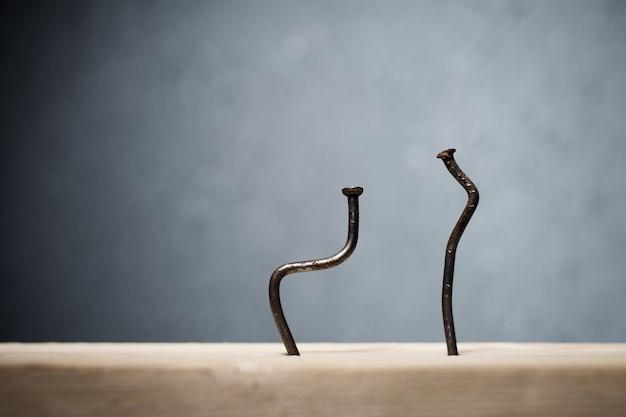 Due chiodi piegati conficcati in una tavola. concetto chinarsi, sciatica e malattia degenerativa del disco