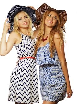 Due migliori amiche ragazze che indossano abiti estivi alla moda e cappelli di paglia, divertendosi insieme.