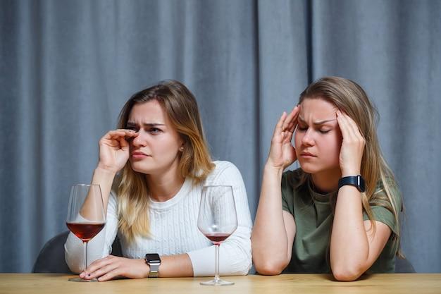 Due migliori amici. giovani donne dall'aspetto europeo che conversano sedute a una scrivania con in mano un bicchiere di vino. le belle ragazze le sorelle adorano bere alcolici ridendo allegramente rilassarsi nel soggiorno