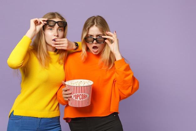 Due giovani sorelle gemelle bionde sconcertate in occhiali 3d imax che guardano film film tenere popcorn isolato su parete blu viola pastello. concetto di stile di vita familiare di persone.