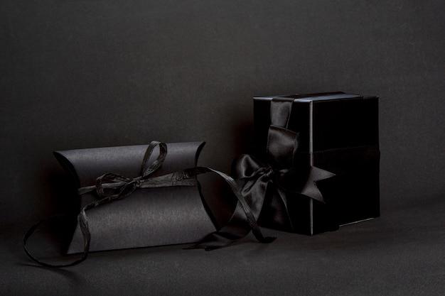 Due scatole regalo nero con fiocco in nastro su sfondo scuro