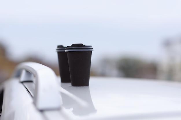 Due bicchieri neri di bevande in uno stand su uno sfondo sfocato della città