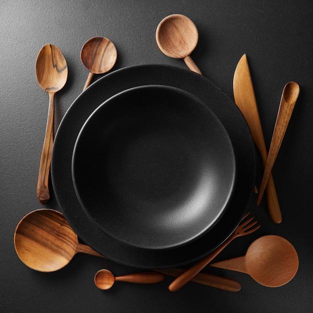 Due piatti neri e cucchiaio di legno, forchetta, coltello su un tavolo nero.