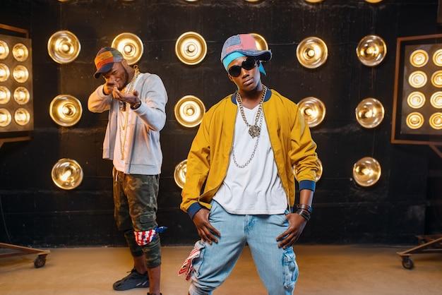Due rapper neri in berretto sul palco con i riflettori