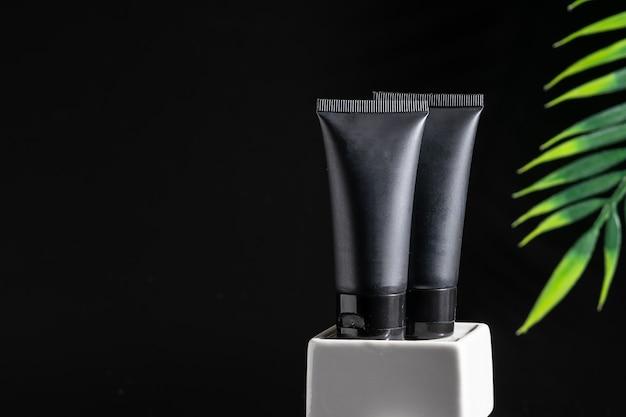 Due tubi neri senza marchio per crema cosmetica, maschera o lozione su sfondo nero con foglia di palma verde.