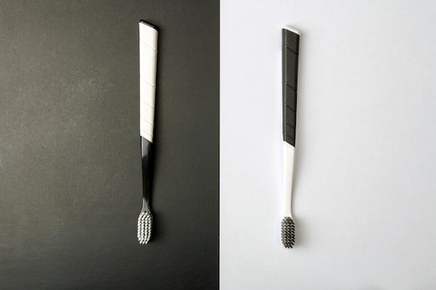 Due spazzolini da denti in bianco e nero su una monocromia.