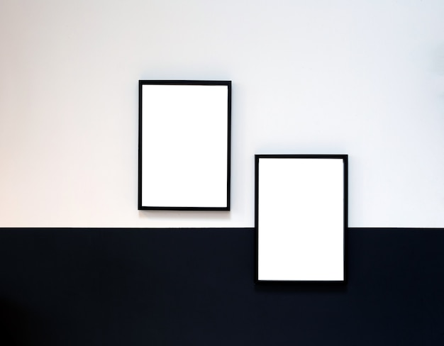 Due poster in bianco, tela, cornice appesa al muro bianco e nero, interni dal design moderno mock up frame copia spazio,
