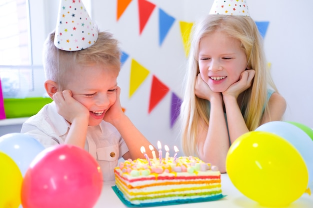Due bambini caucasici biondi, ragazzo e ragazza, si divertono a spegnere le candeline alla torta arcobaleno di compleanno con