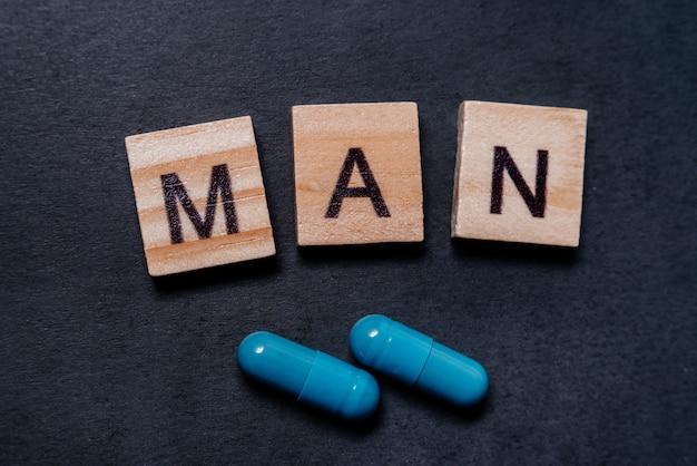 Due capsule blu e l'uomo delle iscrizioni. pillole per la salute e l'energia sessuale degli uomini su sfondo nero. concetto di erezione, potenza. trattamento di infertilità e impotenza maschili.