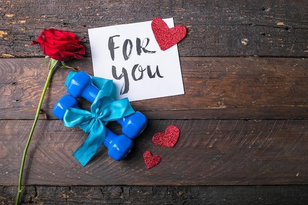 Due manubri blu con un fiocco regalo e tag di carta bianca, cuore su assi di legno, concetto di vacanza sportiva