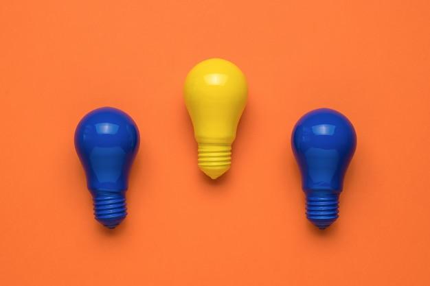 Due lampadine blu e una gialla su sfondo arancione. minimalismo. disposizione piatta.