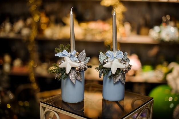 Due vasi blu con composizione di decorazioni natalizie di rami di abete, stelle giocattolo, foglie d'argento e ornamenti e candele