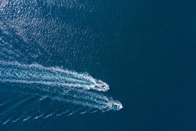 Due barche che galleggiano sul mare alla vista del drone ad alta velocità.