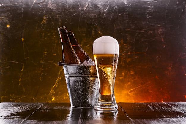 Due bottiglie di birra in un secchio con ghiaccio e un bicchiere di birra con schiuma lussureggiante