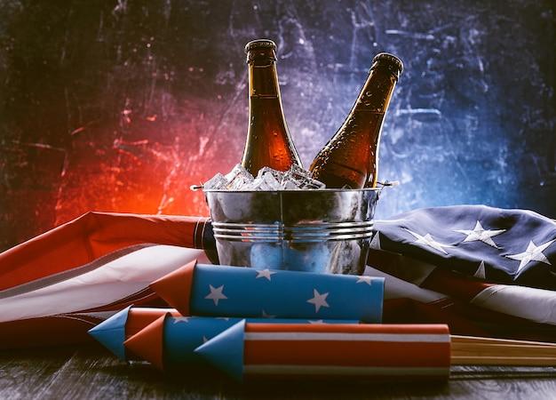 Due bottiglie di birra in un secchiello del ghiaccio con la bandiera americana che giace nelle vicinanze e razzi per fuochi d'artificio. concetto di celebrazione del giorno dell'indipendenza