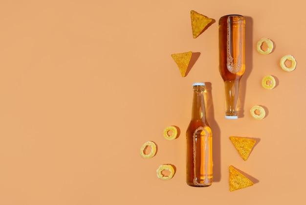 Due bottiglie di birra artigianale e birra porter e snack nachos e pistacchi su sfondo beige. concetti della giornata internazionale della birra o dell'oktoberfest. foto minimalista. copia spazio