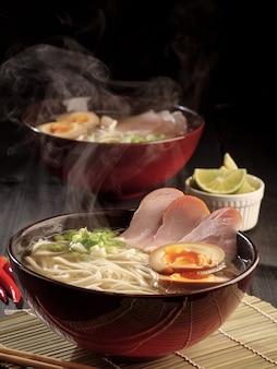 Due ciotole di ramen di maiale caldo e uova in salamoia al vapore. foto verticale.