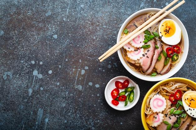 Due ciotole di zuppa di noodle giapponese ramen con brodo di carne, fette di maiale, narutomaki, uova con tuorlo su fondo di pietra rustico. piatto tradizionale del giappone, vista dall'alto, primo piano, concetto. spazio per il testo