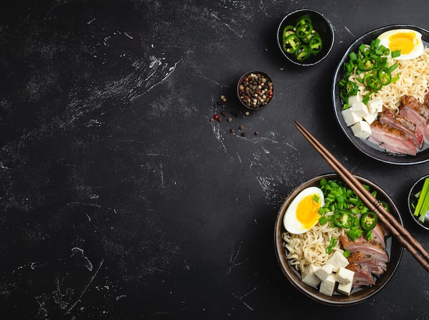 Due ciotole di gustosa zuppa di noodle asiatici ramen con brodo, tofu, maiale, uova su fondo di pietra rustico nero, spazio per il testo, primo piano, vista dall'alto. zuppa calda e gustosa di ramen giapponese per cena con spazio per le copie