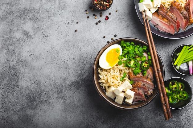 Due ciotole di gustosa zuppa di noodle asiatici ramen con brodo, tofu, maiale, uova su fondo di cemento rustico grigio, spazio per il testo, primo piano, vista dall'alto. zuppa calda e gustosa di ramen giapponese per cena con spazio per le copie