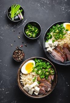 Due ciotole di gustosa zuppa di noodle asiatici ramen con brodo di carne, tofu, maiale, uova con tuorlo su fondo di cemento rustico nero, primo piano, vista dall'alto. zuppa calda e gustosa di ramen giapponese per cena in stile asiatico