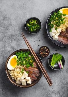 Due ciotole di gustosa zuppa di noodle asiatici ramen con brodo di carne, tofu, maiale, uova con tuorlo su sfondo grigio cemento rustico, primo piano, vista dall'alto. zuppa calda e gustosa di ramen giapponese per cena in stile asiatico