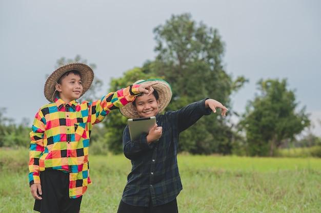Due persone asiatiche ragazzo utilizzando tablet in piedi fuori porta agricoltore, concetto smart agricoltore o scuola di studio collage di istruzione