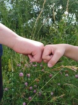 Due mani di ragazzo si stringono la mano in natura