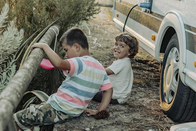 Due ragazzi in una roulotte che giocano nella natura