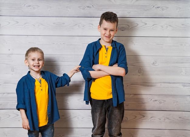 Due ragazzi in abiti casual in legno bianco che guarda l'obbiettivo