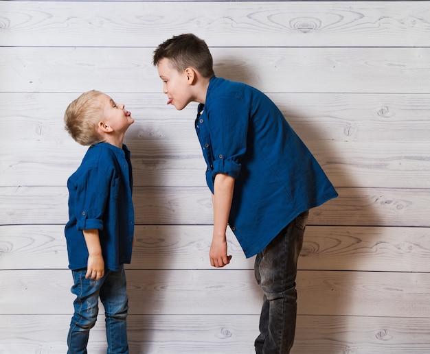 Due ragazzi in abiti casual in legno bianco che mostrano lingue l'un l'altro