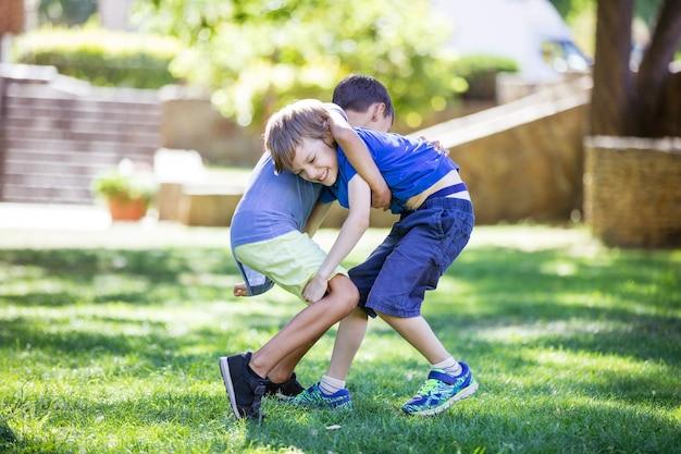 Due ragazzi che combattono all'aperto. fratelli o amici che lottano nel parco estivo. rivalità tra fratelli.
