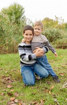 Due ragazzi che si divertono insieme all'aperto. famiglia felice. fratelli che si abbracciano