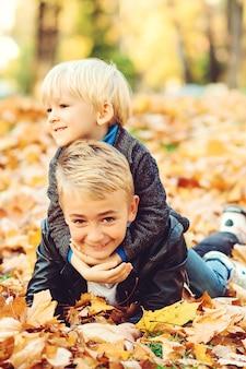 Due ragazzi che giocano in foglie d'autunno. infanzia felice e sana. bambini svegli divertendosi insieme nel parco di autunno.